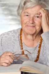 Smiling Elderly Woman Holding Glasses with a Book