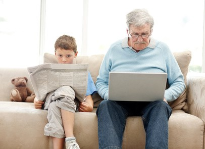 Child Reading Newspaper and Elderly Man on a Laptop
