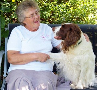 Smiling Elderly Woman Holding Dogs Paw