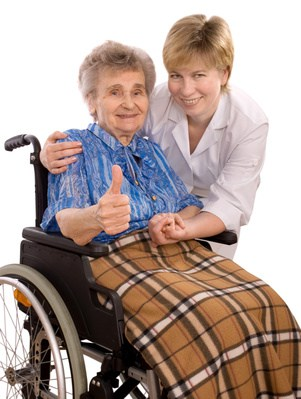 Smiling Nurse Posing with an Elderly Woman in a Wheelchair