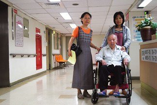 Two Women Pushing an Elderly Man in a Wheelchair