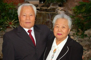 Elderly Couple Posing in Front of Waterfall