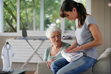Woman With folded Towels Sitting With Elder Loved One