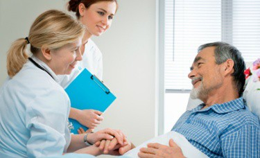Doctor and Nurse Speaking with Elderly Male Patient