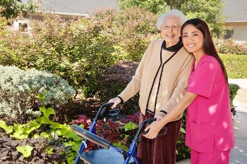 Female Nurse Posing Outside with Elder Patient