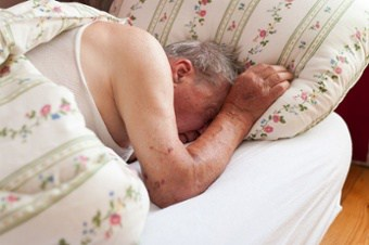 Elderly Man Sleeping in a Bed
