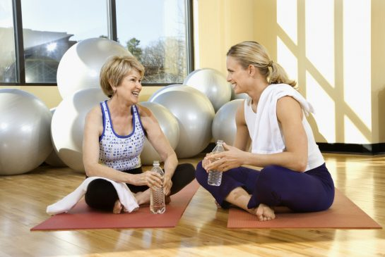 Woman and Older Woman Sitting on Yoga Mats
