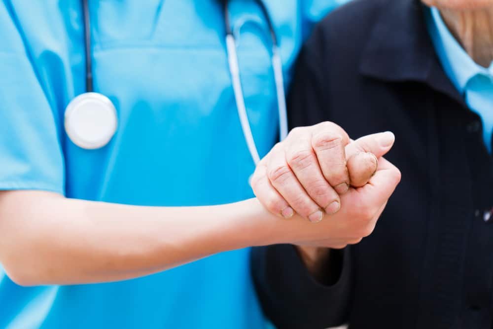 nurse holding the hand of the senior
